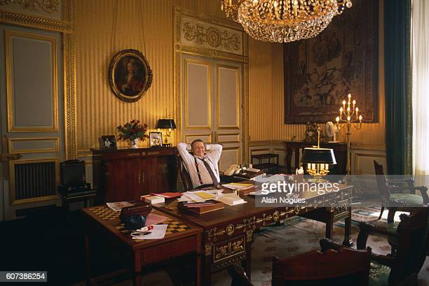French Minister of Finance Michel Charasse sits with hands behind his head relaxing at his desk