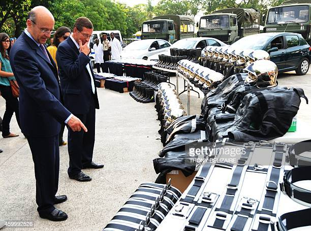 French Minister of Foreign Affairs Alain Juppe looks at the police materials sent from France to the Haitian police May 14 2011 during his visit to...