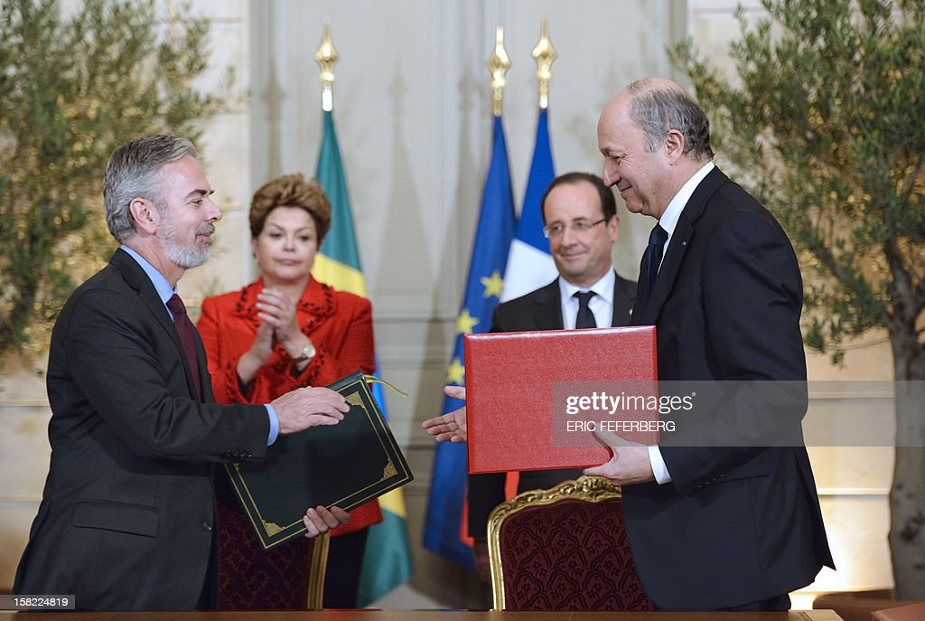 French Minister of Foreign Affairs, Laurent Fabius (R) and his Brazilian counterpart Antonio Patriota (L) shake hands in front of French President Francois Hollande (2ndR) and Brazil's President Dilma Rousseff (2ndL), during an agreement signature ceremony, on December 11, 2012, at the Elysee presidential palace in Paris. During her first official two-day visit to France, Brazilian President Dilma Rousseff will have talks with French counterpart Francois Hollande on the eurozone crisis -- on which she has criticized EU austerity measures -- bilateral trade and wider matters of global concern.
