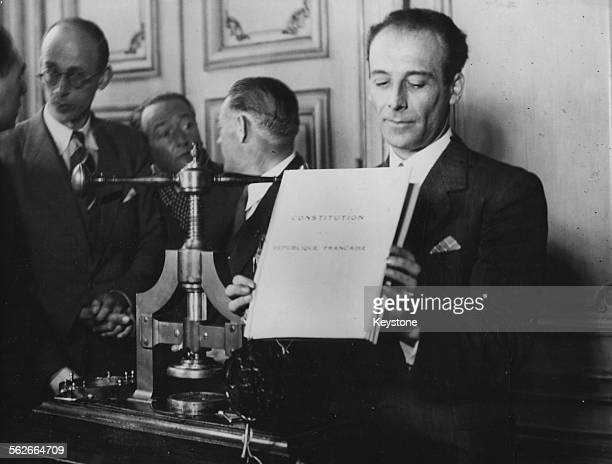 French minister of Justice PierreHenri Teitgen holding up the printed Constitution before putting the Seal of the Republic on it Paris circa 1945