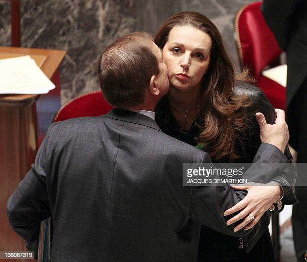 French Minister of Relations with Parliament Patrick Ollier kisses Valerie Boyer UMP rightwing ruling party deputy on December 22 2011 in Paris at...