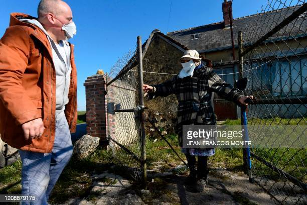 TOPSHOT French mobile baker and grocer Arnault Carnis chats with a 92yearold woman who wears a makeshift face mask in front of her house after...