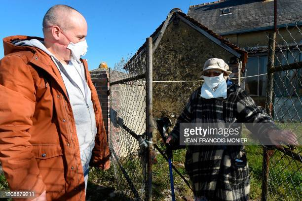 French mobile baker and grocer Arnault Carnis chats with a 92yearold woman wearing a makeshift face mask and golding a crutch in front of her house...