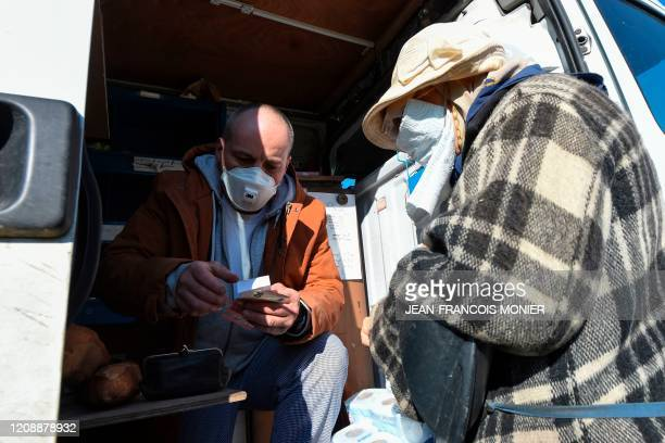 French mobile baker and grocer Arnault Carnis gives back change after selling supplies to a 92yearold woman who wears a makeshift face mask in front...