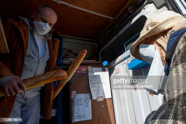 French mobile baker and grocer Arnault Carnis gives bread and other supplies to a 92yearold woman who wears a makeshift face mask in front of her...