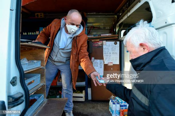 French mobile baker and grocer Arnault Carnis wearing a face mask gives change to a client after seeling him supplies in Combres western France on...