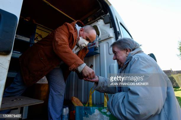 TOPSHOT French mobile baker and grocer Arnault Carnis wearing a face mask gives change to a resident of Combres western France on April 1 on the...