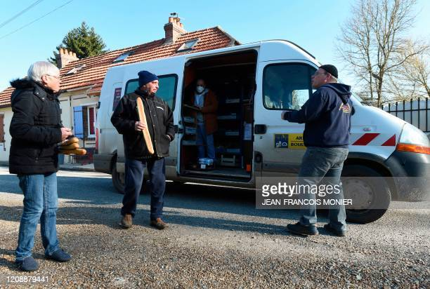 French mobile baker and grocer Arnault Carnis wearing a face mask sells supplies to residents of Combres western France on April 1 on the sixteenth...
