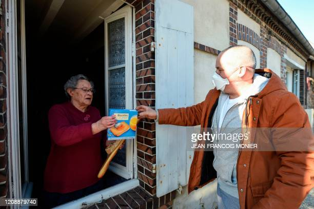 French mobile baker and grocer Arnault Carnis wearing a face mask delivers bread and supplies through the window of a resident of Combres western...