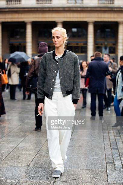 French model and actress Aymeline Valade wears a gray varsity jacket and loose white trousers after the Isabel Marant show on Day 4 of PFW FW16 on...