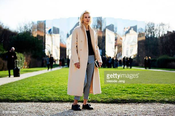 French model and actress Aymeline Valade wears a pink coat black shirt black and white gingham trousers and black shoes at the Dior Couture show at...