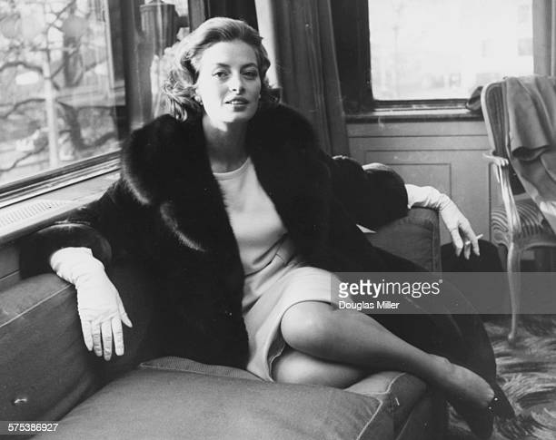 French model and actress Capucine pictured smoking a cigarette and wearing a fur coat and gloves at a reception in her honor at the Savoy Hotel...