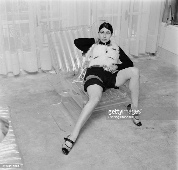 French model and fashion designer Emmanuelle Khanh sitting in a transparent plastic armchair, UK, 27th July 1967.