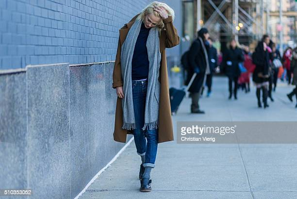 French model Aymeline Valade wearing dark blue denim jeans a grey scarf and a brown coat seen outside Lacoste during New York Fashion Week Women's...