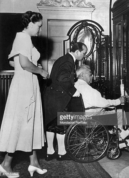 French model Begum Om Habibeh Aga Khan escorting her husband Imam of the Nizari Ismaili community Aga Khan III sitting on a wheelchair 1950s