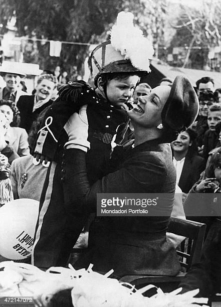 French model Begum Om Habibeh Aga Khan fourth wife of Imam of the Nizari Ismaili community Aga Khan III hugging a child dressed as a gendarme Le...