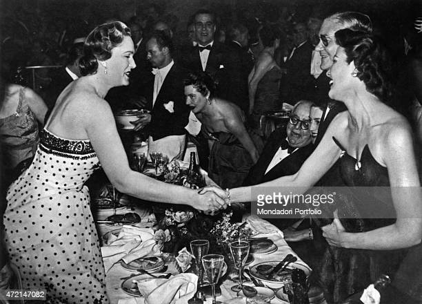 French model Begum Om Habibeh Aga Khan shaking hands with American actress Gene Tierney Her husband Imam of the Nizari Ismaili community Aga Khan III...