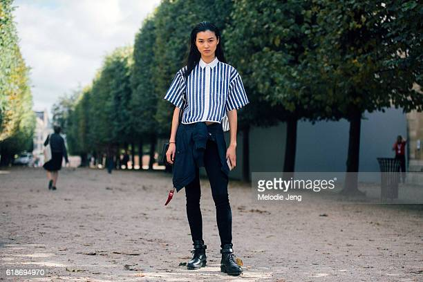 French model Estelle Chen wears a blue and white Sacai striped top Alpha Industries flight jacket around her waist black Paige jeans and chunky black...
