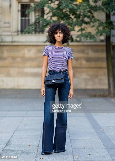 French model Melodie Vaxelaire wearing flared denim jeans and Chanel bag and striped top on September 28 2016 in Paris France