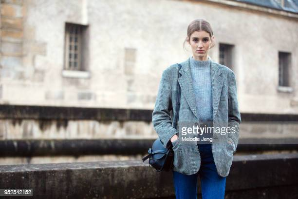 French model Nina Fresneau wears a plaid blazer gray sweater Loewe small Gate midnight blue bag and jeans after the Valentino show on March 04 2018...