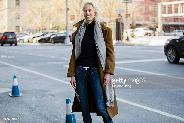 French model/actress Aymeline Valade attends the Lacoste show in a camel coat gray scarf Lacoste navy sweater and jeans at Spring Studios during New...