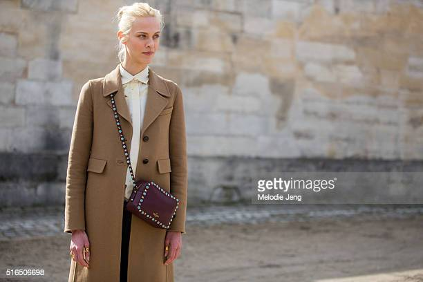 French model/actress Aymeline Valade wears a beige wool coat and red Valentino studded purse at the Valentino show at the Tuileries on March 07 2016...