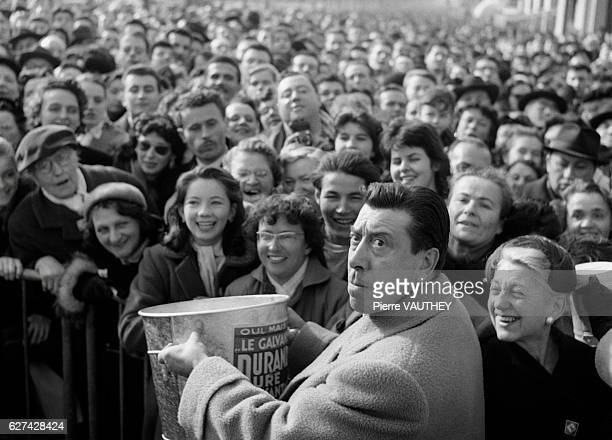 French motion picture actor Fernandel carries a bucket past fans during the Gala de la Kermesse aux Etoiles