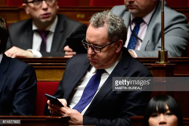 French MP and La Republique en Marche party group president Richard Ferrand checks his mobile phone during a session of questions to the government...