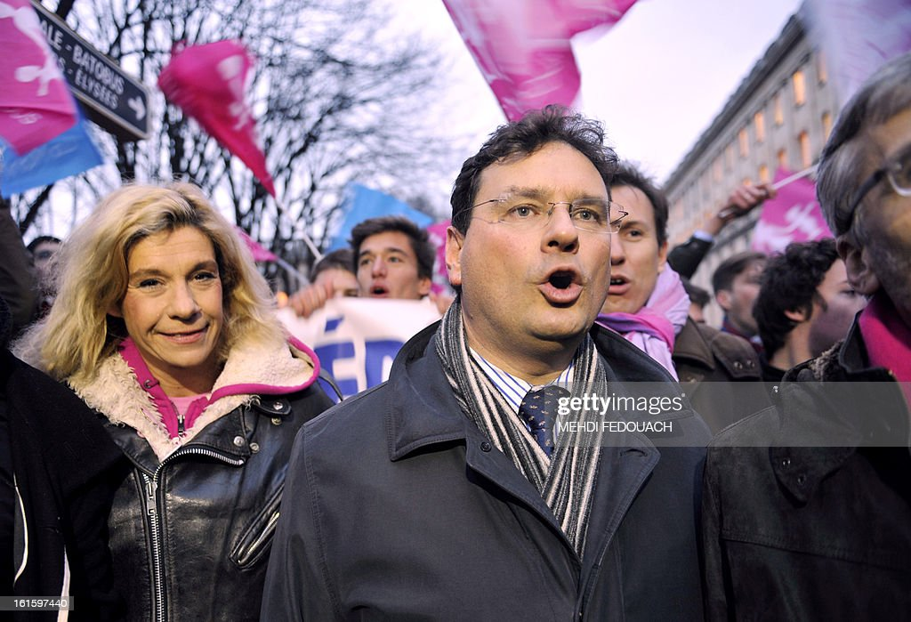 French MP Philippe Gosselin (R) and French humorist Virginie Tellene, aka 'Frigide Barjot,' chant slogans as they walk with other activists toward French National Assembly in Paris, to protest while members of the National Assembly vote on legalising same-sex marriage. France's Parliament examined draft legislation on same-sex marriage after months of rancorous debate and huge street protests by both supporters and opponents.