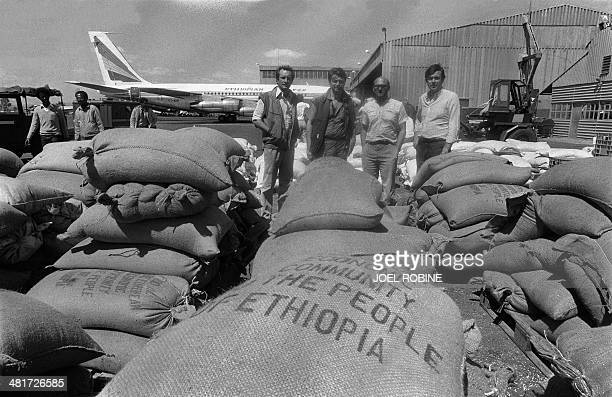 French MP's delegation Gérard Longuet Alain Madelin Michel Sapin and JeanJack Queyranne pose in front of tons of rice and grain unloaded from...