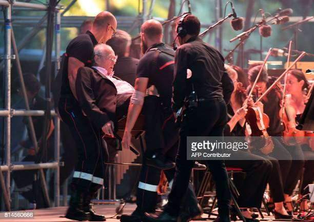 TOPSHOT French music composer Michel Legrand is carried away by French firefighters after fainting on stage during a commemorative ceremony marking...