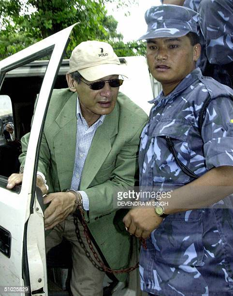 French national Charles Sobhraj is assisted by a Nepalese policeman as he steps out of a jeep wearing handcuffs as he arrives for a hearing at a...