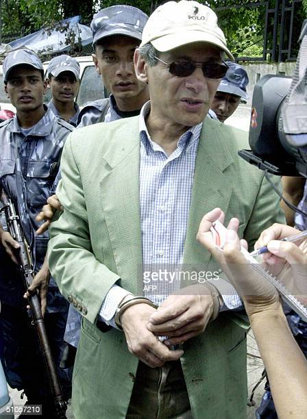 French national Charles Sobhraj talks to media representatives as he arrives escorted by armed police officers at a District Court in Kathmandu 14...