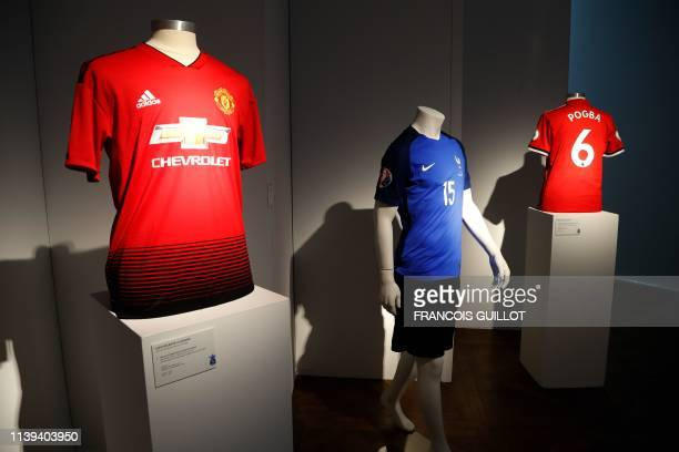A French national football team and Manchester United jerseys worn by French midfielder Paul Pogba are displayed at Christies auction house on April...