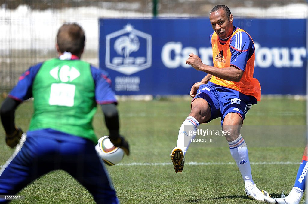French national football team's captain Thierry Henry (R) scores in front of his teammate, goalkeeper Cedric Carraso during a training session, on May 25, 2010, near Tignes in the French Alps, as part of the preparation for the upcoming World Cup 2010. France will play against Uruguay in Capetown in its group A opener match on June 11.