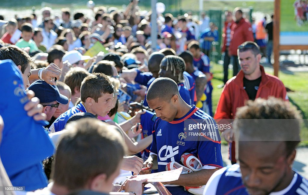 French national football team's defender Gael Clichy (C) signs a autographs after a training session, on May 24, 2010, near Tignes in the French Alps, as part of the preparation for the upcoming World Cup 2010. France will play against Uruguay in Capetown in its group A opener match on June 11.