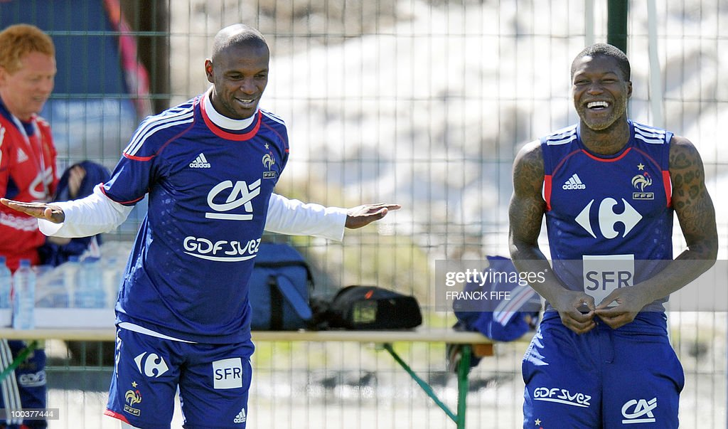 French national football team's Eric Abidal (L) jokes with Djibrill Cisse during a training session, on May 24, 2010, near Tignes in the French Alps, as part of the preparation for the upcoming World Cup 2010. France will play against Uruguay in Capetown in its group A opener match on June 11.