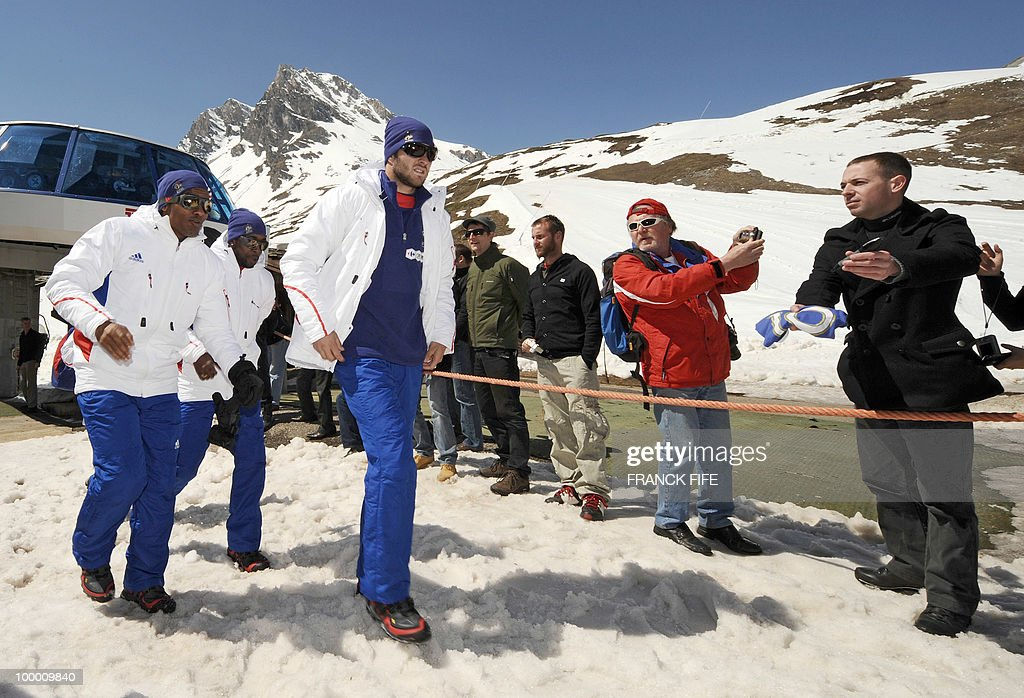 French national football team's forward Florent Malouda, midfielder Sidney Govou and forward Andre-Pierre Gignac are photographed by fans as they arrive in Tignes, French Alps, on May 20, 2010 after having spent the night with teammates at the top of a glacier. The French national team slept in altitude last night, as part of their altitude training in preparation for the 2010 World cup in South Africa.
