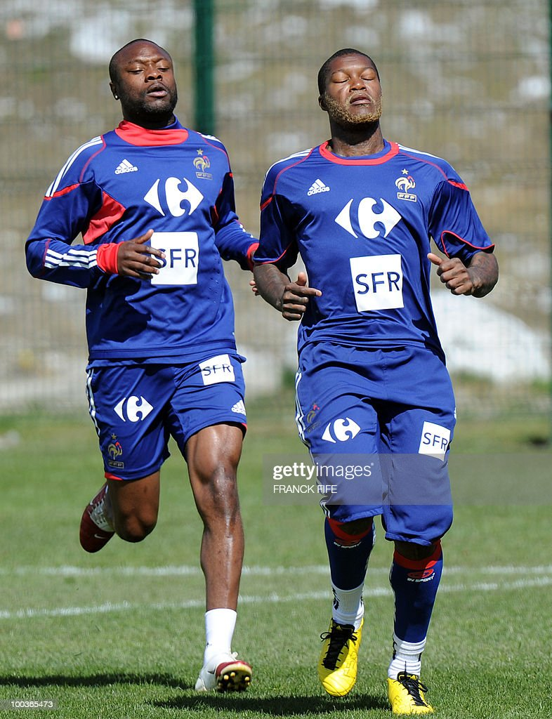French national football team's players William Gallas (L) and Djibrill Cisse run during a training session, on May 24, 2010, near Tignes in the French Alps, as part of the preparation for the upcoming World Cup 2010. France will play against Uruguay in Capetown in its group A opener match on June 11.