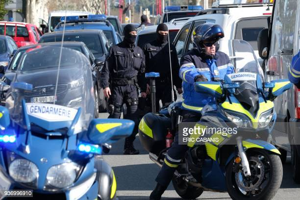 French National Gendarmerie Intervention Group and gendarmes stand next to vehicles as they gather outside the Super U supermarket in the town of...