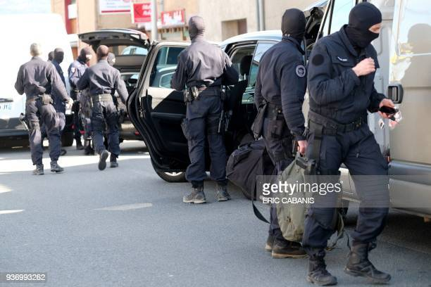 TOPSHOT French National Gendarmerie Intervention Group stand next to vehicles as they gather outside the Super U supermarket in the town of Trebes...