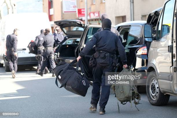 French National Gendarmerie Intervention Group stand next to vehicles as they gather outside the Super U supermarket in the town of Trebes southern...