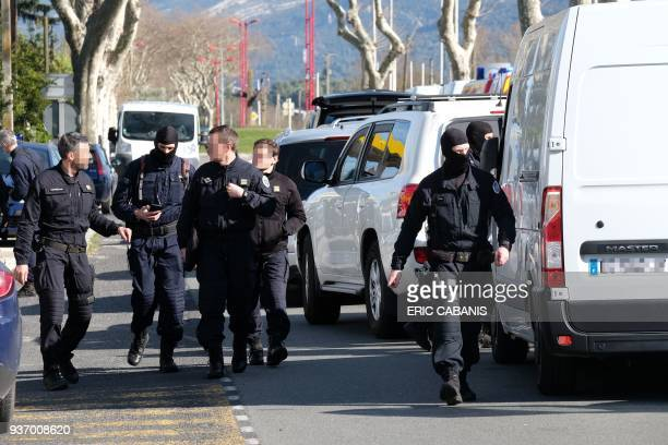 French National Gendarmerie Intervention Group walk next to vehicles as they gather outside the Super U supermarket in the town of Trebes southern...