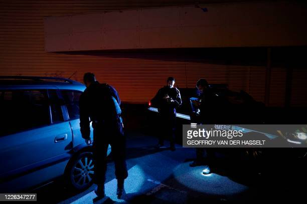 French National Gendarmerie PSIG-Sabre surveillance and intervention members inspect a stolen car during a night patrol, in Villabe, south of Paris,...