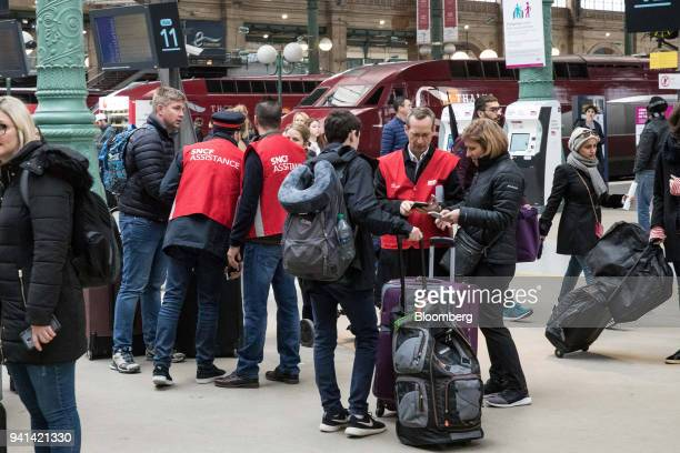 French national railway operator workers assist travelers during industrial strike action by railway workers and other labor union members at Gare du...