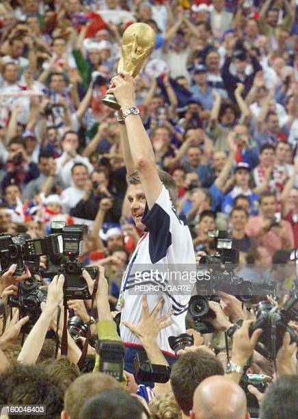 French national soccer team coach Aime Jacquet celebrates holding aloft the FIFA Trophy 12 July at the Stade de France in SaintDenis near Paris after...