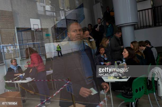 French nationals arrive to vote at the Lycee Francais Charles de Gaulle in London on April 23 as voting begins in the first round of the 2017 French...