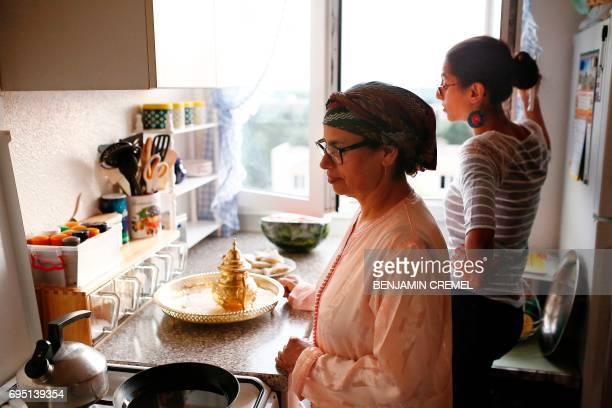 French nationals Zhorand her daughter Asmaa prepare a traditional Iftar meal in preparation of breaking their fast during the Islamic holy month of...