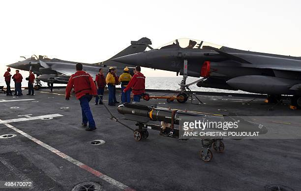 French navy engineers install a bomb on a French Rafale fighter aircraft aboard the French CharlesdeGaulle aircraft carrier on November 23 2015 at...