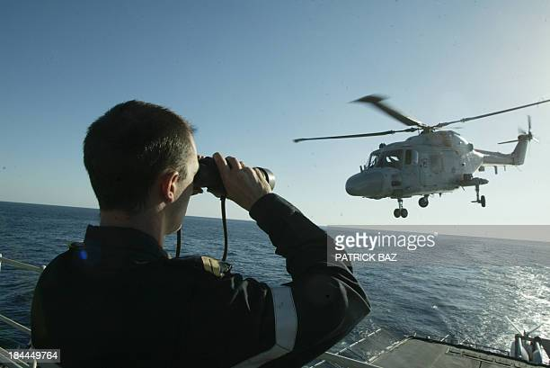 A French Navy helicopter takes off from the Fregate Tourville while a sailor scans the Red Sea looking for debris during a search mission conducted...